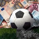 Un pallone da calcio in una montagna di soldi