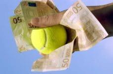 Una mano che stringe delle banconote da 50 euro e una pallina da tennis