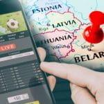 Uno smartphone connesso su un sito scommesse online, una mano che sta per premere sul display, la mappa della Bielorussia sullo sfondo