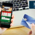 Il logo di H2 Gambling Capital, uno smartphone con la schermata di un sito di betting online, una carta di credito e la tastiera di un laptop su una scrivania