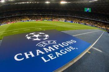 Uno stadio con le squadre che si scaldano prima dell'inizio di una partita di Champions League, con il logo della manifestazione in primo piano