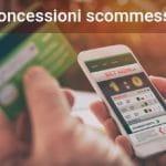 Due mani reggono nella destra uno smartphone collegato al sito di un bookmaker online e nella sinistra una carta di credito