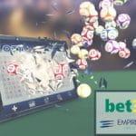 Tavolo da gioco, tablet da cui escono palloni, logo Bet365, logo Empire Resorts