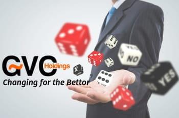 Un uomo in giacca e cravatta lancia dei dadi da gioco dalla mano sinistra, con il logo di GVC Holdings e quello di Changing for the Bettor