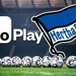Una serie di palloni da calcio disposti in uno stadio, con i loghi di MoPlay e dell'Hertha Berlino