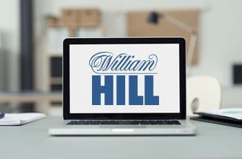 Un computer portatile con il logo di William Hill posato sulla scrivania di un ufficio