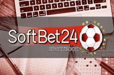 Il logo di SoftBet24 e sullo sfondo la tastiera di un laptop con una schedina, una penna e una matita