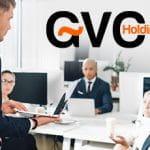 Un gruppo di persone sedute a una scrivania in un ufficio e il logo di GVC