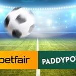 Un pallone da calcio e, sullo sfondo, uno stadio illuminato durante un match notturno, con i loghi di Betfair e Paddy Power