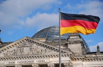 Il palazzo che ospita il Parlamento federale tedesco a Berlino e la bandiera della Germania