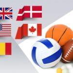 Dei palloni da basket, pallavolo, football americano, delle palline da ping pong e una palla da baseball in un guantone, con le bandiere di Stati Uniti, Regno Unito. Danimarca, Canada e Romania