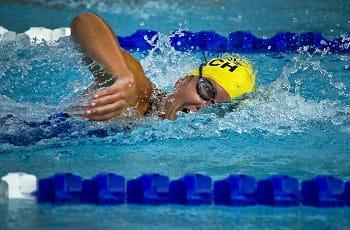 Una nuotatrice con la cuffia gialla in azione