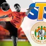Un giocatore di calcio in azione e i loghi di STS e Zaglebie Lubin