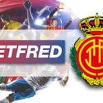 Calciatori in azione e i loghi di Betfred e RCD Maiorca