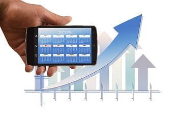 Uno smartphone con un calendario e un grafico con una freccia