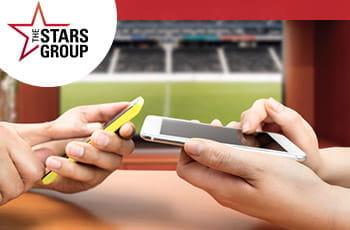Il logo di Stars Group, due smartphone e un campo da calcio in sottofondo