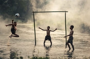 Alcuni bambini che giocano a calcio in riva al mare