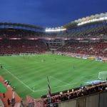 Uno stadio di calcio affollato durante una partita in notturna