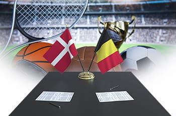 Le bandiere di Danimarca e Belgio, una scrivania e dei palloni di diversi sport