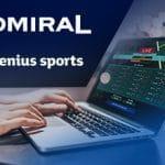 Il logo di Admiral, il logo di Genius Sports, un laptop e una mano che scrive