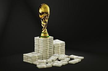 Una riproduzione della Coppa del Mondo di calcio sopra delle mazzette di banconote
