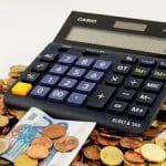 Una calcolatrice, delle monete e delle banconote