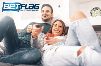 Una ragazza e un ragazzo su un divano mentre guardano la tv e il logo di BetFlag