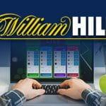 Una persona davanti a un laptop e il logo di William Hill