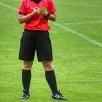 Un arbitro di calcio sanziona con un cartellino giallo