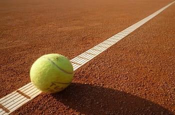 Una pallina da tennis rimbalza su un campo di terra rossa