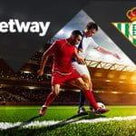 Il logo di Betway, il logo del Betis Siviglia, due calciatori in azione