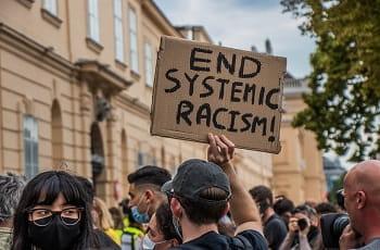 """Una manifestazione antirazzista e un cartello con la scritta """"Stop al razzismo sistemico"""" in inglese"""