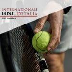 Il logo degli Internazionali d'Italia di tennis e un tennista alla battuta
