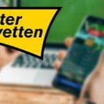 Il logo di Interwetten e uno smartphone collegato a un bookmaker online