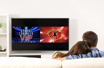 Una coppia guarda la televisione, con i loghi del Grande Fratello Vip e di Ballando con le Stelle