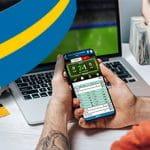Uno scommettitore davanti a uno smartphone e a un laptop e la bandiera della Svezia