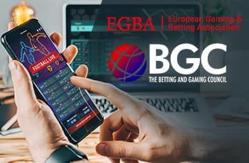 I loghi di EGBA e BGC e uno smartphone collegato a un bookmaker online