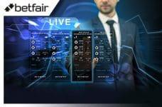 Il logo di Betfair, la schermata di un bookmaker online e un uomo in giacca e cravatta
