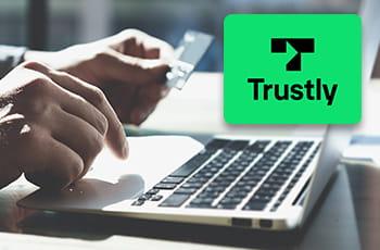 Il logo di Trustly e la tastiera di un computer