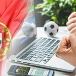 La bandiera del Portogallo, un laptop e delle mani strette a pugno
