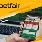 Il logo di Betfair e uno smartphone sulla pagina di un bookmaker online