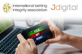 I loghi di IBIA e Jdigital e uno smartphone collegato a un sito scommesse online