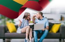 Una coppia esulta davanti a un laptop e la bandiera della Lituania