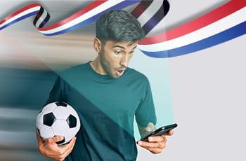 Un ragazzo con un pallone e uno smartphone e la bandiera dell'Olanda