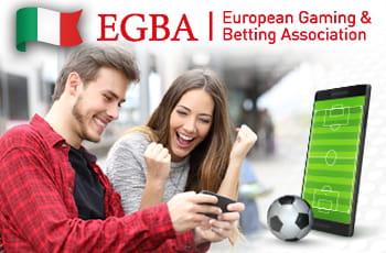 Il logo di EGBA, la bandiera dell'Italia e un ragazzo e una ragazza davanti allo schermo di un computer