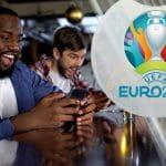 Il logo di Euro 2020 e dei ragazzi che scommettono in un pub