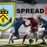 I loghi del Burnley FC e di Spreadex e dei calciatori in azione