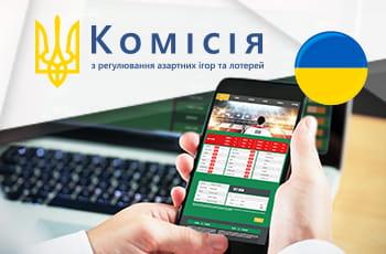 Il logo della gambling commission ucraina (KRAIL) e uno smartphone collegato al sito di un bookmaker online