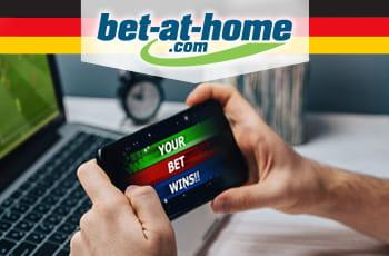 Il logo di bet-at-home, la bandiera tedesca e un telefonino collegato a un bookmaker online