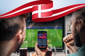 Persone che scommettono e bandiera della Danimarca.